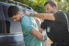 He will have to serve a drunk-driving sentence. Shot of a policeman handcuffing a young driver Stock Photos