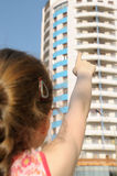 We will live there. Girl is pointing at block of flats stock photo