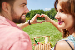 Will love you forever. A photo of young, happy couple celebrating their anniversary on the picnic at the park. They're putting their hands together in the heart royalty free stock image