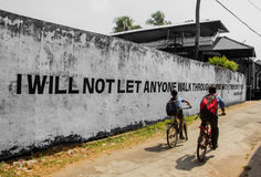 We will not let anyone wwalk trough my mind with their dirty fee. Two boys ride in front of a mural with a sentence by Mahatma Gandhi Stock Image