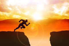 Will Power. Silhouette illustration of a male figure sprinting to jump the ravine Stock Photos