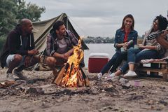They will remember this day. Group of young people in casual wear smiling while enjoying beach party near the campfire royalty free stock image