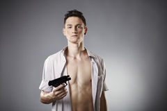 Will he use it?. Young man with shaped body posing in studio with handgun for like criminal portraits Royalty Free Stock Image