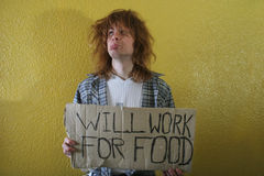 Will work for food. Hungry young man holding a cardboard with text Stock Photos