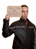 Will Work For Gas. A male holding a sign saying he will work for gas, isolated on a white background Royalty Free Stock Images