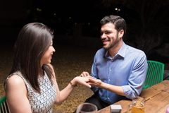 Will You Be Mine Forever. Happy men proposing his lover with engagement ring at party in restaurant stock photos