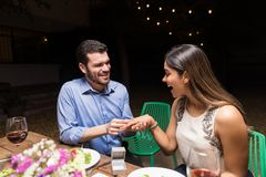 Will You Be My Forever. Smiling young men surprising women with engagement ring at backyard party royalty free stock image
