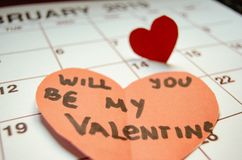 Will you be my Valentine - Paper red hearts marking 14 february Valentines day on white calendar stock image