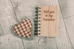 Will you be my Valentine Text on wooden notebook and wooden hear Stock Image