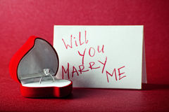 Will you marry me. Red box with diamond ring and card with text on red background Stock Photo
