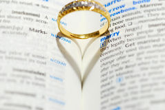Will you marry me. Wedding ring casting a heart onto a marry word royalty free stock images