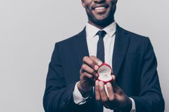 Will you marry me? Cropped close up photo of happy cheerful exci. Ted man dressed in smart suit holding a red box with engaging ting, isolated on grey background Stock Photos