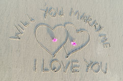 Will you marry me. And Heart drawn on sand. Sign of romantic and love Stock Image