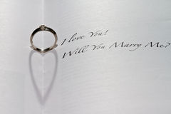 Will You Marry Me Ring. Ring casting heart shadow in book with the sentence I Love You! Will You Marry Me Royalty Free Stock Image
