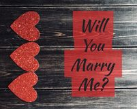 Will you marry me sign. Will you marry me text with red glitter heart border on a wooden background Royalty Free Stock Images