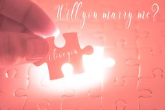 Will you marry me word on pink jigsaw puzzle being holding by th. E hands of men. Valentines day concept marriage and wedding proposal Royalty Free Stock Photography