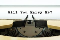 Will you marry me word on a yellow vintage typewriter. Valentines day concept. Marriage and wedding proposal.  stock photos