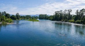 Willamette River Oregon. Wide expanse of Willametter river in Eugene Oregon as seen from bridge with trees and mountains, blue sky and clouds Stock Photo