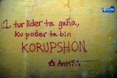 Willemstad, Curacao, Slogan in Papiamento painted on an old wall. Willemstad, Curacao, Slogan painted on a wall `When a leader comes to power corruption comes stock photos