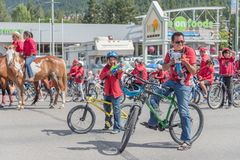 Group of cyclists spray crowds with water guns at parade. Williams Lake, British Columbia/Canada - July 2, 2016: man and boy riding bicycles stop to spray water Royalty Free Stock Images