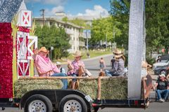 Man and children wave from farm themed parade float. Williams Lake, British Columbia/Canada - July 2, 2016: people in western dress wave to the crowds from their Stock Image