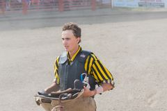 Cowboy stands read with saddle at Wild Horse Race royalty free stock images