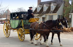 Williamsburg, VA: Coachman, Horses and Coach. Visitors to Colonial Williamsburg, Virginia enjoy riding in an 18th century coach driven by a costumed driver and Royalty Free Stock Photography