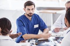 Willing lekarz słucha jego kolegów przy konferencją zdjęcie royalty free