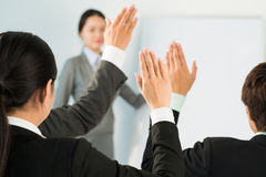 Willing to answer. Business people raising hands to answer in training Stock Photography