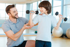 Willing to be strong and healthy. Happy father helping his sun with weight exercises while both standing in health club Royalty Free Stock Photo
