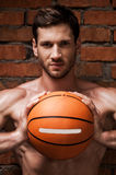 He is willing to this game. Handsome young muscular man holding basketball ball while standing against brick wall Royalty Free Stock Photo