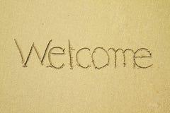 Willkommen geschrieben auf Sand am Strand Stockfotos