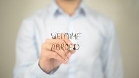 Willkommen im Ausland, Mann-Schreiben auf transparentem Schirm Stockfotos