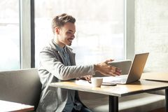 Willkommen! Porträt des erfüllten glücklichen jungen Mannes im grauen Blazer sitzen im Café und grüßen eine Arbeitskraft durch ei stockbilder