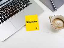 Willkommen or welcome with smiley face icon on desk stock photo