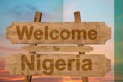 Willkommen zu Nigeria-Zeichen auf hölzernem Hintergrund mit Mischungsstaatsflagge lizenzfreies stockfoto