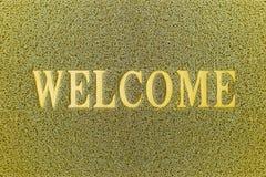 Willkommene gelbe Tür-Matte Willkommener Teppich-Hintergrund Stockfotos