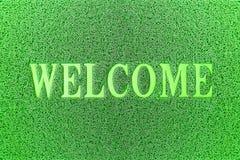 Willkommene grüne Tür-Matte Willkommener Teppich-Hintergrund Stockbilder