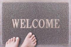 Willkommene Tür Mat With Female Feet Freundliches Grey Door Mat Closeup mit der bloßen Frauen-Fuß-Stellung Willkommener Teppich Stockfotografie