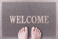 Willkommene Tür Mat With Female Feet Freundliches Grey Door Mat Closeup mit der bloßen Frauen-Fuß-Stellung Willkommener Teppich Stockbilder