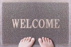 Willkommene Tür Mat With Female Feet Freundliches Grey Door Mat Closeup mit der bloßen Frauen-Fuß-Stellung Willkommener Teppich Stockfoto