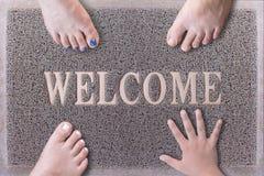 Willkommene Tür Mat With Three Feet und eine Hand Stockbild