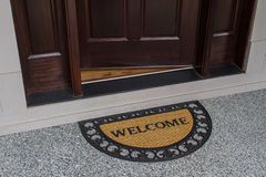 Willkommene Türmatte mit offener Tür lizenzfreies stockfoto