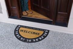Willkommene Türmatte mit offener Tür und Person lizenzfreie stockbilder