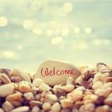 Willkommener Text geschrieben auf den Stein am Strand Stockbilder