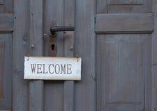 Willkommensschild, das an einer alten Holztür hängt Lizenzfreies Stockfoto