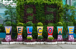 Willkommensschildwort auf Blumentöpfen Stockfoto