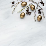 Willow and alder branches, golden eggs on Carrara marble counter. Willow and alder branches, golden eggs on Carrara marble kitchen worktop, easter concept Stock Image