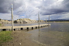 Willow Lake Boat Dock Prescott Arizona. A scenic of beautiful willow lake near prescott arizona with granite rock formations and impending storm clouds and boat Stock Photo