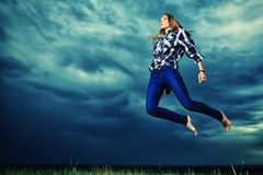 Willpower. Beautiful young woman jumping in the field over stormy evening sky Royalty Free Stock Photography
